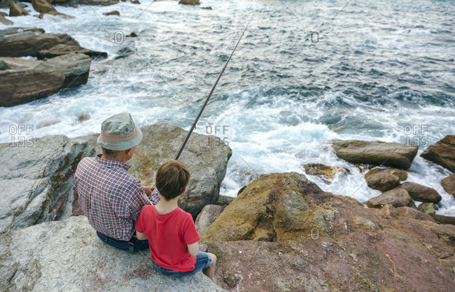 Grandfather and grandson fishing together at the sea sitting on rock