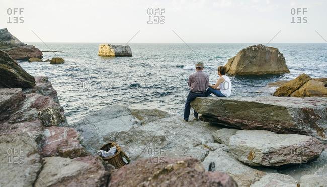Senior couple fishing at the sea sitting on rock