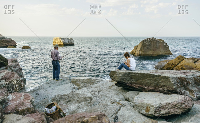 Senior man fishing at the sea with wife sitting on rock