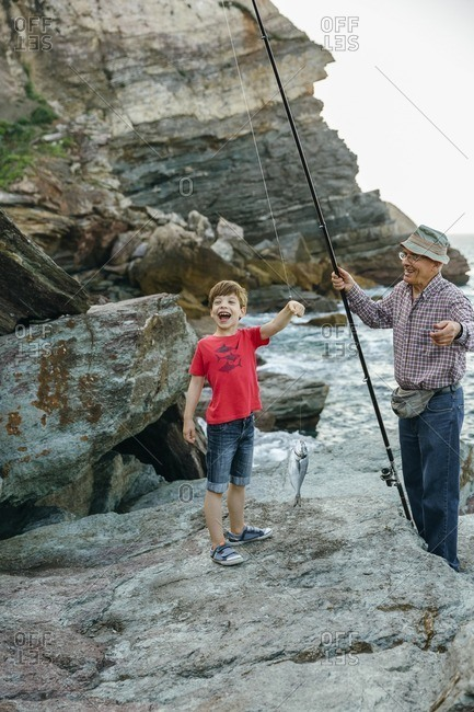 Happy boy holding fish on fishing line caught by his grandfather