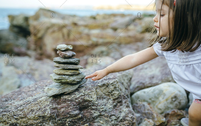 Girl with stack of stones at rocky coast