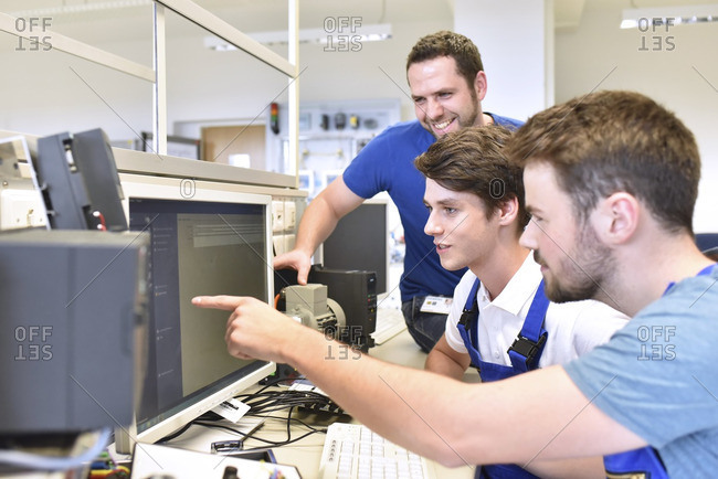Technical instructor and students looking at computer screen