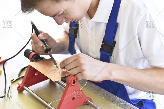 Student assembling circuit board - Offset