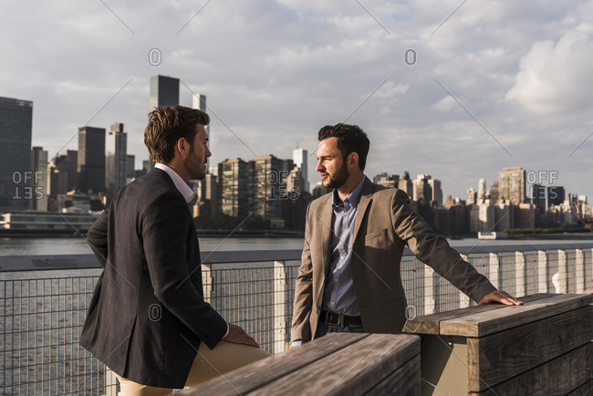 USA- New York City- two businessmen talking at East River