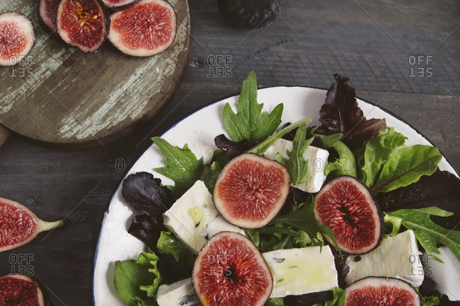 Plate of mixed lettuce with fresh figs- goat cheese and olive oil