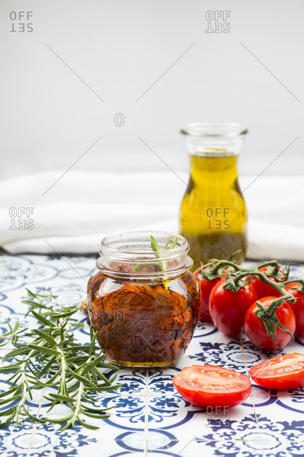 Glass of pickled dried tomatoes and ingredients