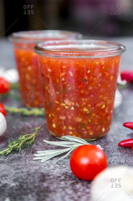 Glasses of homemade tomato sauce and ingredients on stone