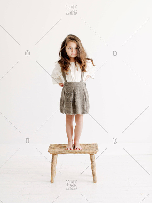 Young girl standing on stool