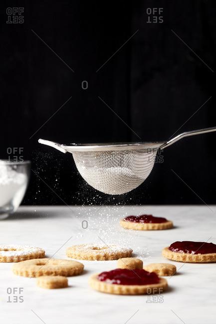 Sprinkling sugar on linzer cookies