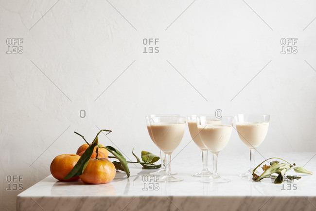 Goblets with cocktails by oranges
