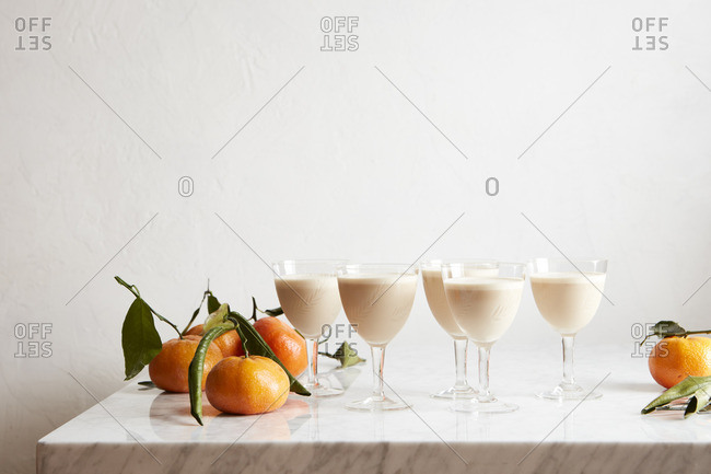 Goblets with cocktail drinks by oranges
