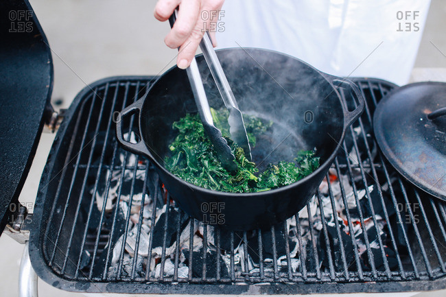 Person cooking greens in a pot over an outdoor grill