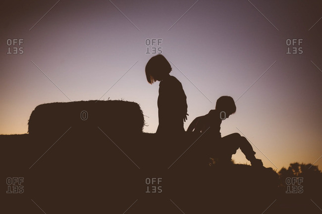 Silhouette of boy and girl playing on hay bales at sunset