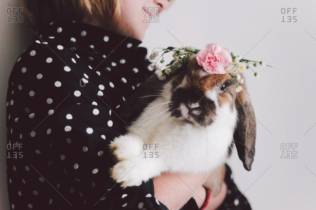 Little girl holding a rabbit with flowers on its head