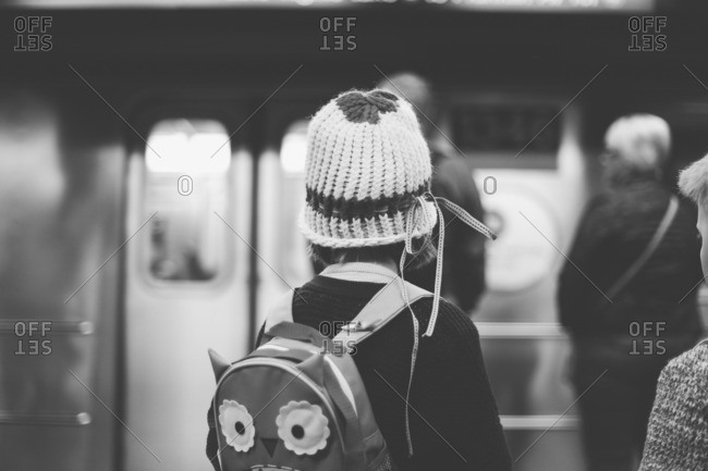 Girl with a knit cap and owl backpack standing in a subway