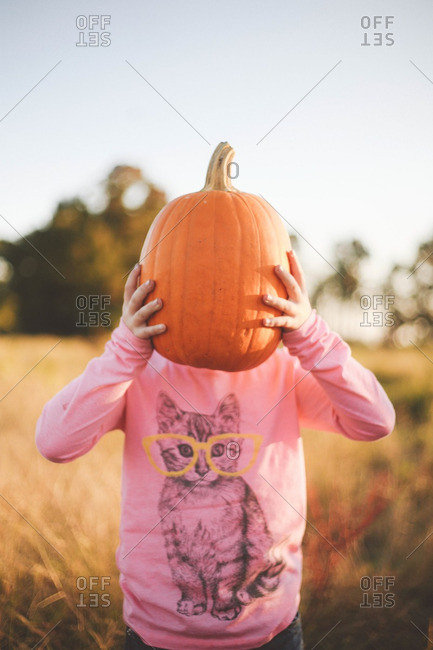 Little girl standing in a field with a pumpkin in front of her face
