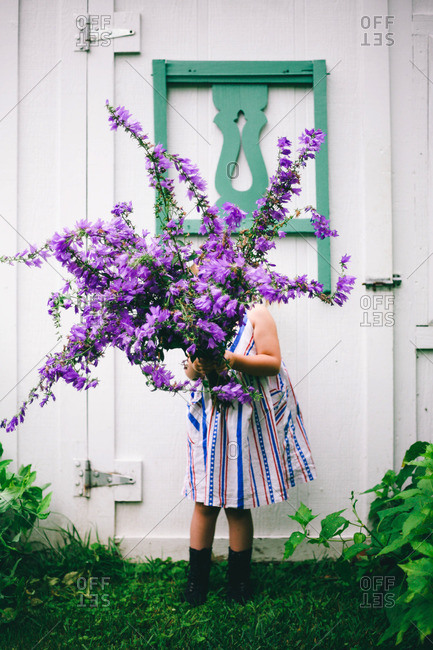 Girl standing in front of a rustic door with large purple flowers