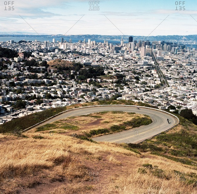 Two men ride bikes around the famous Twin peaks bend overlooking the San Francisco skyline