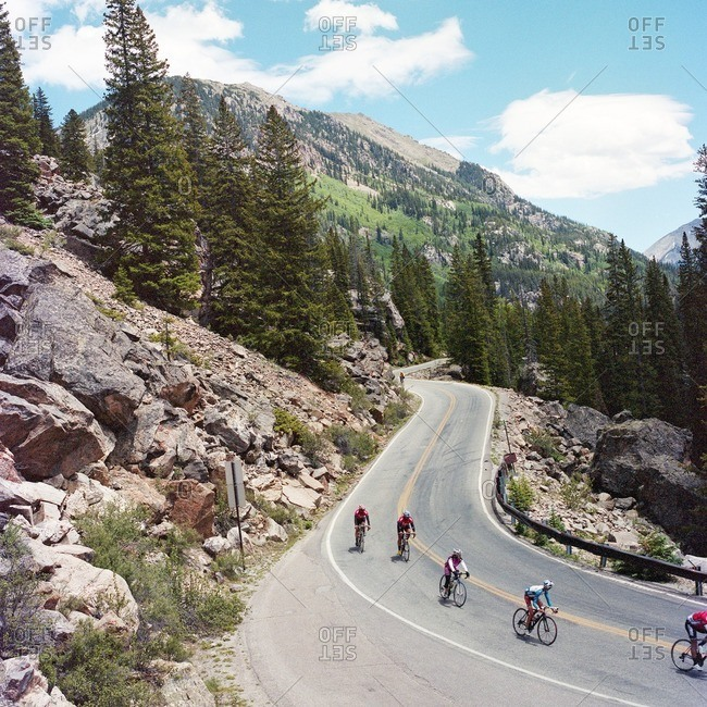 Men and women descending mountain road during bicycle tour of Colorado