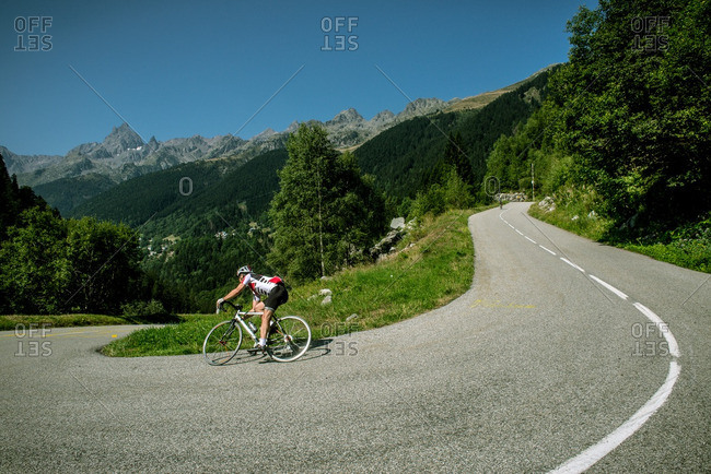 A man on a road bike turns a sharp corner on a Mountain pass of the French Alps