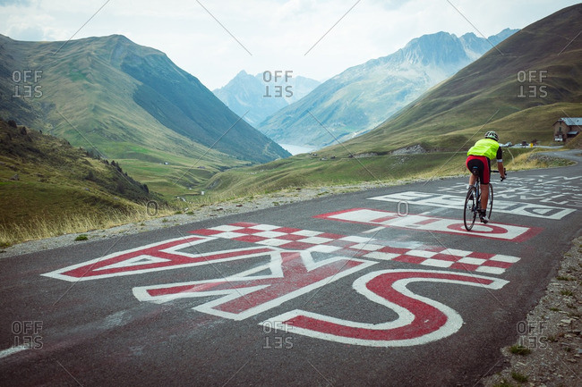 A man on a road bike passes over a painted road on the Col Du Glandon, a famous route of the Tour De France in the French Alps