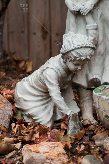 Statue of little girl kneeling by a bird bath