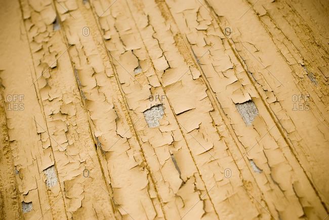 Peeling yellow paint on building exterior