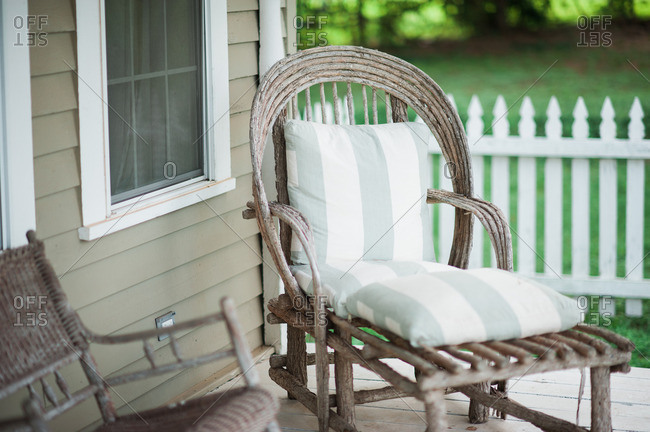 Wooden chair with cushions on a front porch