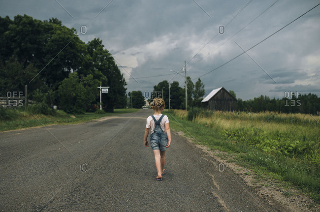 Rear view of a little girl walking on a country road