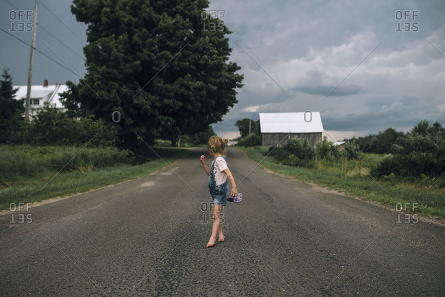 Little girl walking on a country road