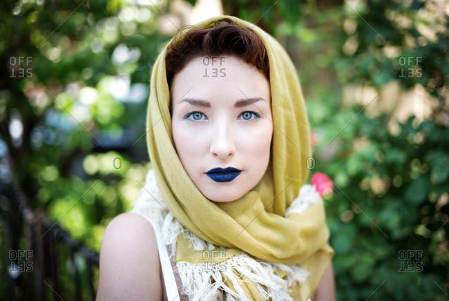 Woman wearing yellow head scarf and blue lipstick