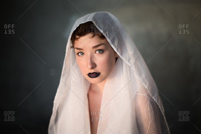 Woman wearing white scarf on her head and dark lipstick