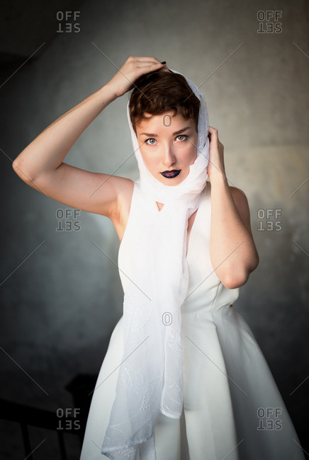Woman wearing white scarf and dress and dark lipstick