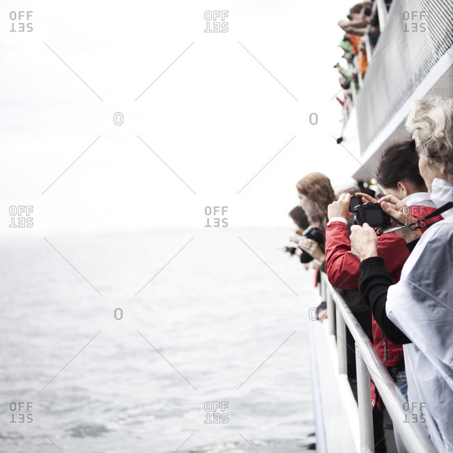 Cape Cod, United States - September 4, 2012: Whale watchers taking photos from the railing of a boat
