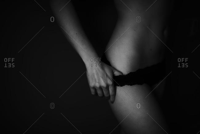 Woman slipping down her black panties