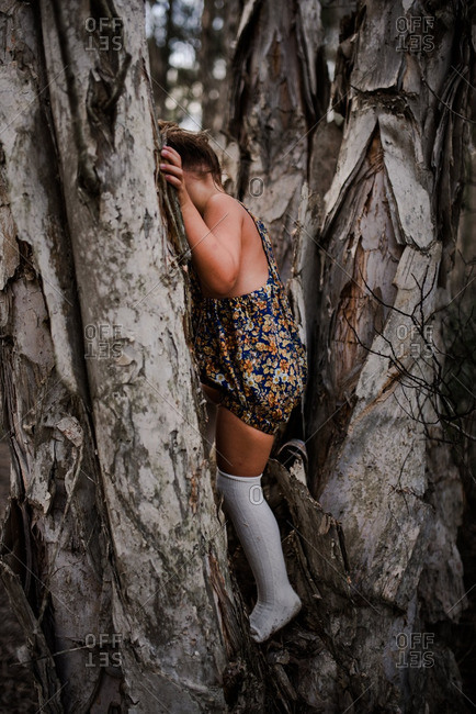 Little girl wearing romper climbing in a tree in the woods