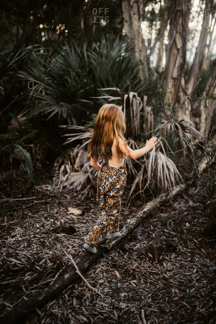Little redhead girl in a romper walking on a fallen tree