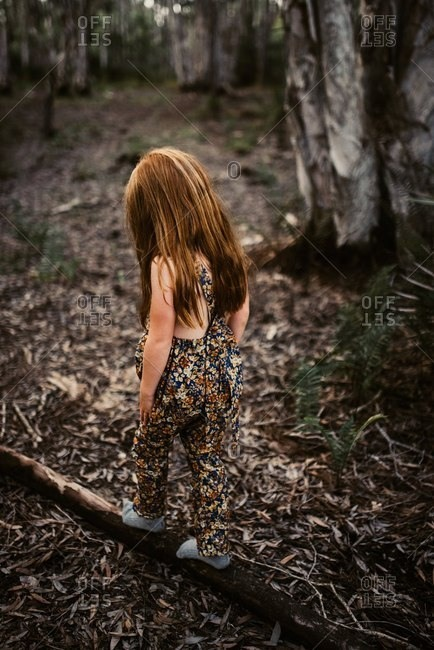Little girl in a romper walking on a fallen tree