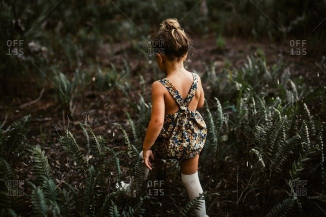 Little girl wearing romper walking in the woods