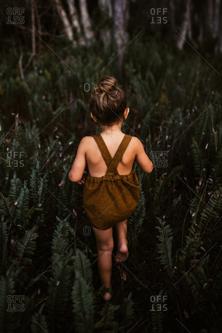 Little girl walking through fern plants in a brown romper