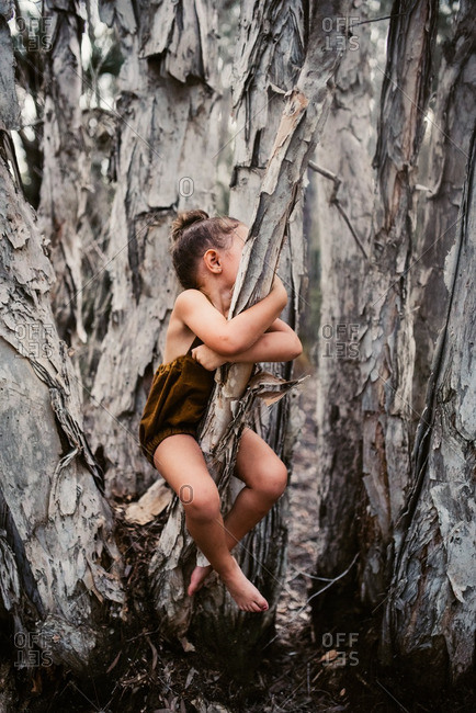 Little girl in a brown romper sitting in a tree