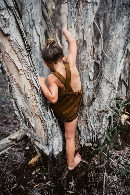Little girl climbing up a tree wearing a brown romper