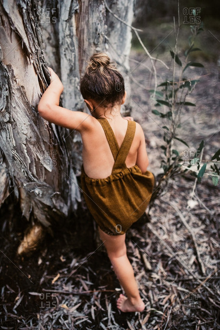 Little girl in a brown romper climbing a tree