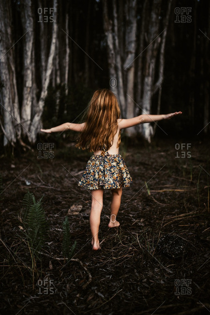 Redhead girl in a romper preparing to do a cartwheel