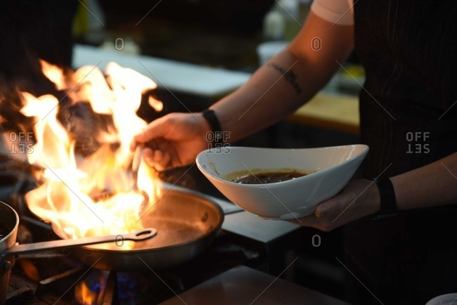 Person pouring a spoonful of liquid on a flaming pan in a kitchen