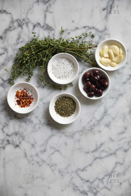 Various seasonings and herbs in bowls on a marble surface