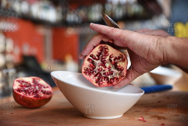 Person holding a halved pomegranate over a bowl
