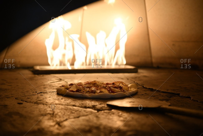 Pizza and paddle in a flaming pizza oven