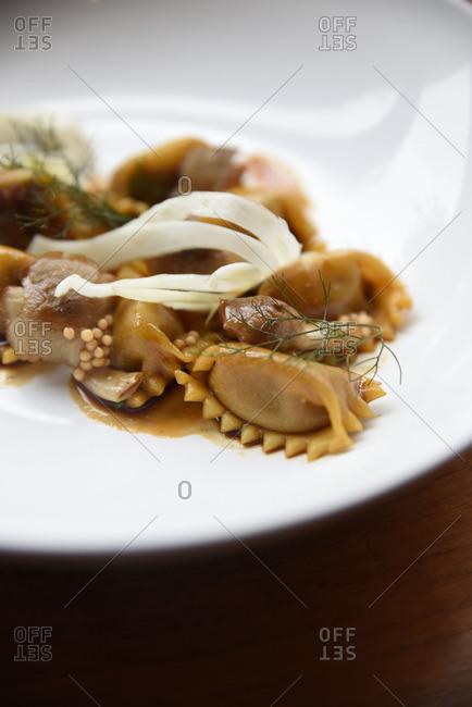 Ravioli in brown sauce in a ceramic dish