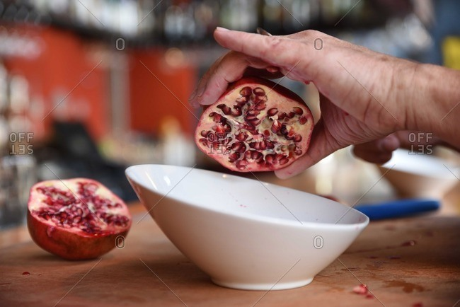 Person removing pomegranate seeds over a bowl